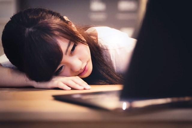 パソコンの前で女性が落ち込んでいる画像