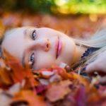 落ち葉に寝転がる少女の画像