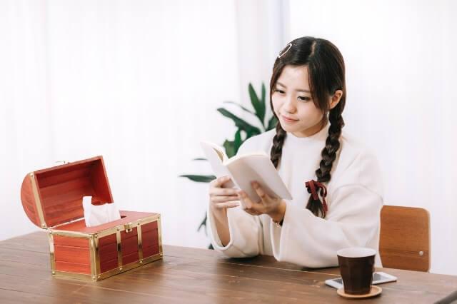 宝箱と読書する女性の画像