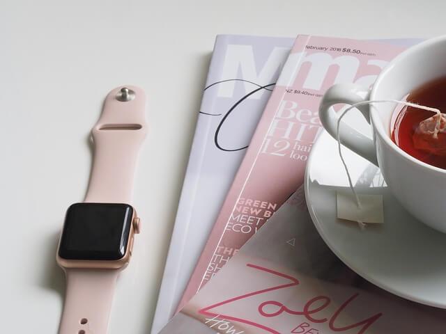 ピンクの時計と雑誌とコーヒーカップ