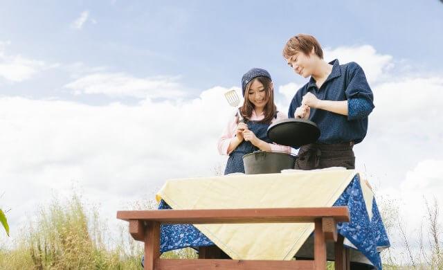 青空の下で料理をする若い夫婦の画像