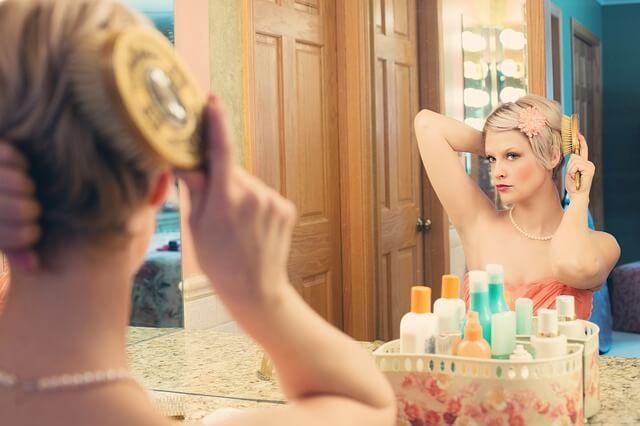 鏡の前でクシを梳かす女性