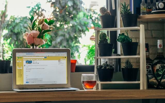 窓際のパソコンと紅茶の画像