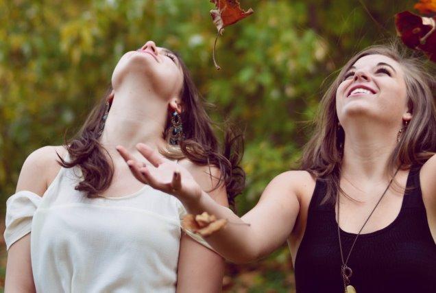 落ち葉を上空に投げ微笑むふたりの女性