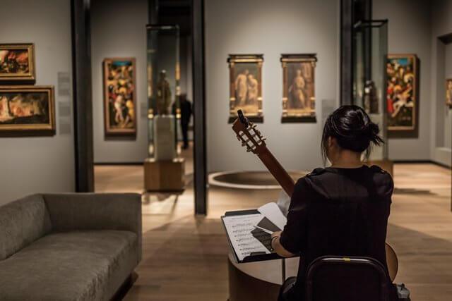 美術館で音楽を奏でる女性の画像
