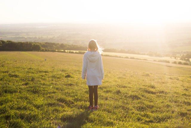 草原でたたずむ少女の画像