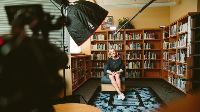 本に囲まれながら撮影される女性の画像