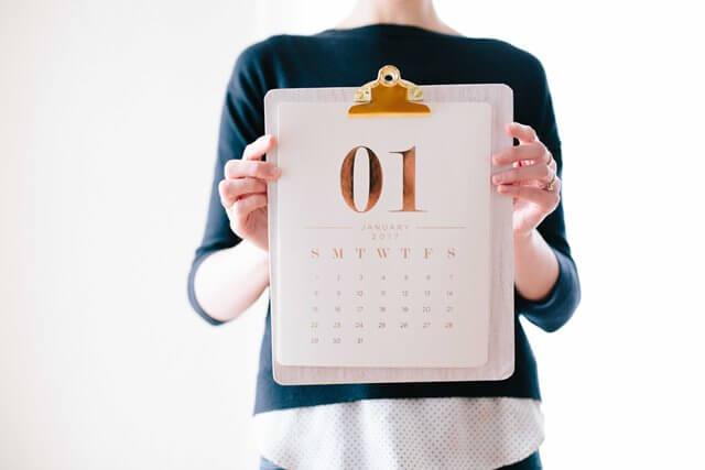 カレンダーを見せる女性の画像