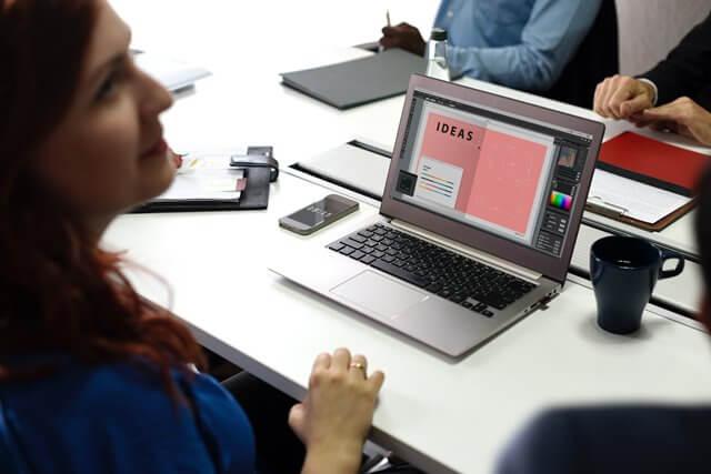 パソコンを使って打ち合わせする女性の画像