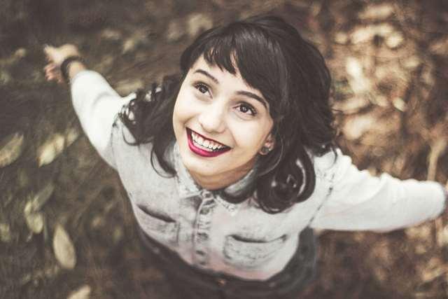 上を見上げ喜ぶ笑顔の女性の画像