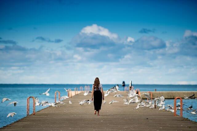 海へ向かって歩く女性の画像