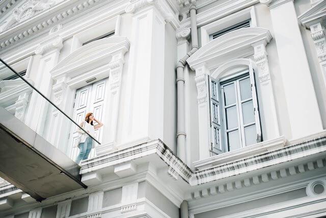 白い建物と高所の女性の画像