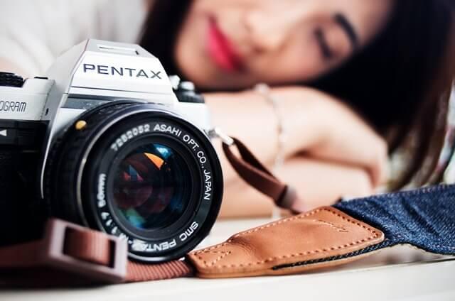 カメラと寝顔の女性の画像