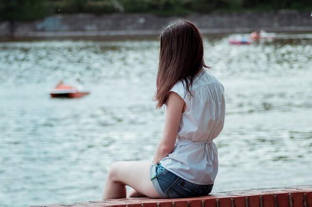 水辺に座る女性の画像