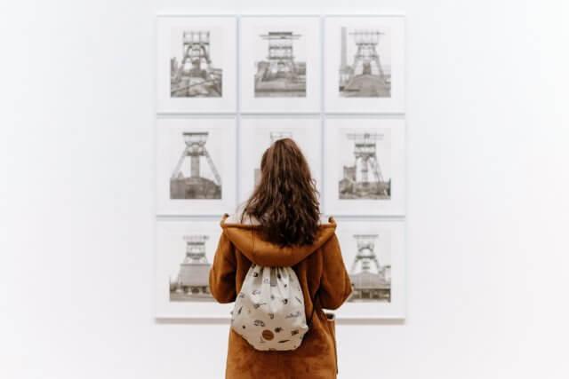 画に魅了される女性の画像