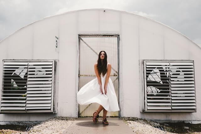 ドアの前に立つ白いドレスの女性の画像