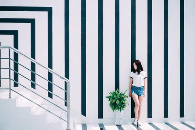 ストライプの壁の前に立つ女性の画像