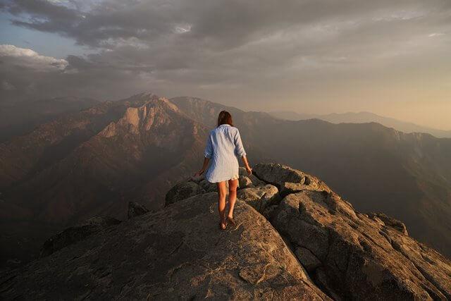 山の頂上を歩く女性の画像