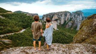 崖上に立つ二人の男女の画像