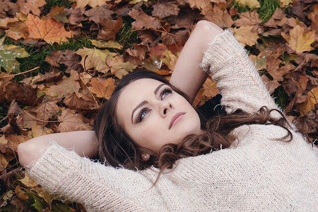 落ち葉の上で考える女性