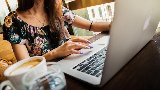 PCの前で作業をする女性とコーヒー