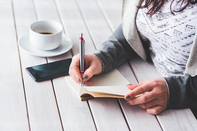 コーヒーを片手にメモをまとめる女性の画像