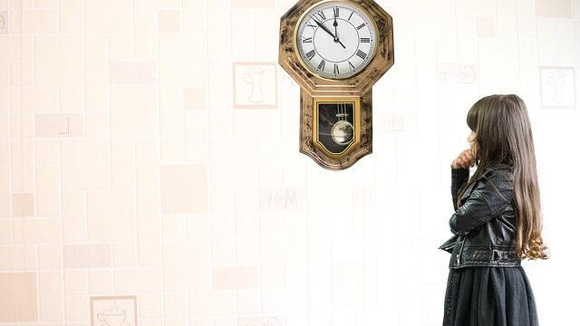 時計を眺める少女の画像