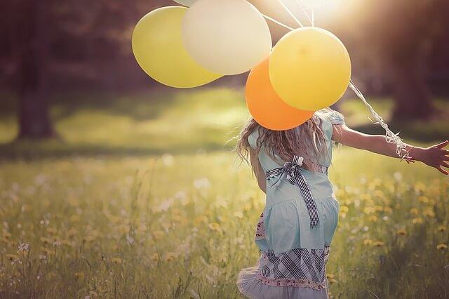 風船を持って駆け出す少女の画像