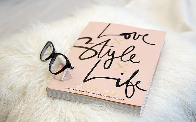 メガネとピンクの背表紙の本