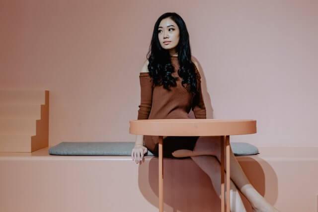 座るロングヘアーの女性